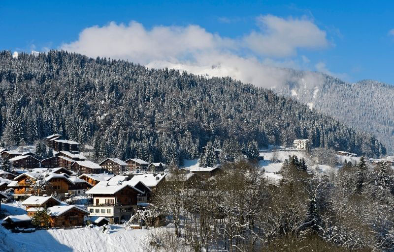 Village in the French alps surrounded by mountains, pine forests and snow