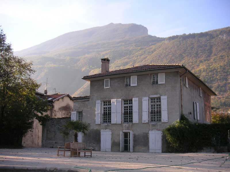 Traditional stone house at the foot of mountains at sun rise