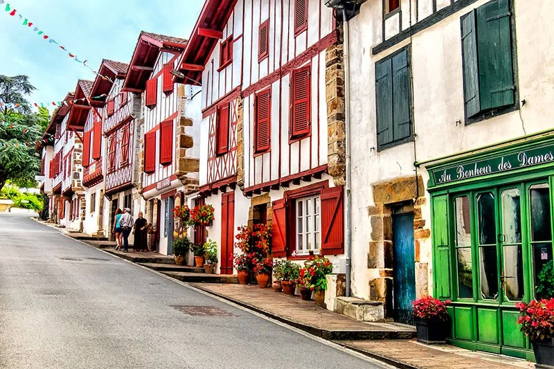 Pretty red and white half timbered houses in a narrow street, Ainhoa, Basque country