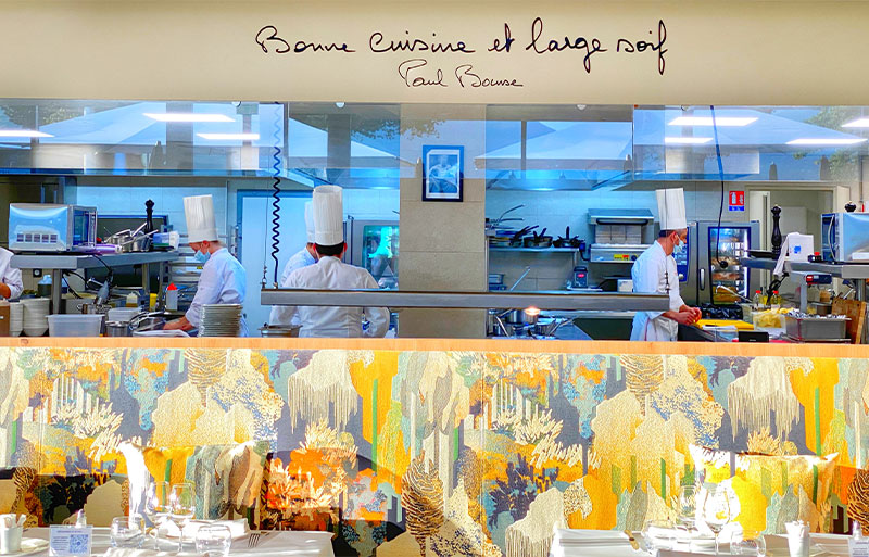 Kitchen of Brasserie Irma Bocuse, Annecy, chefs in tall hats