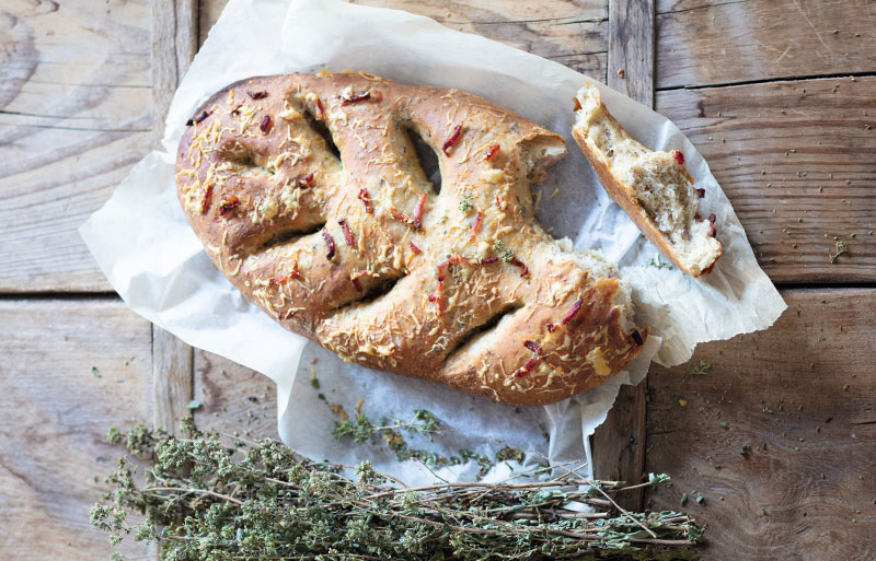 Fougasse loaf with tomato and herb topping with a bunch of thyme