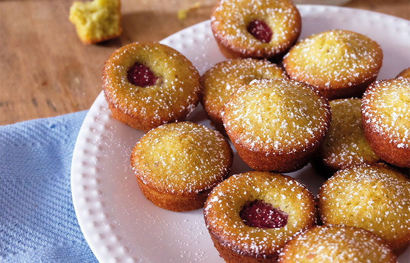 Plate of sponge cakes some with raspberries, sprinkled with sugar