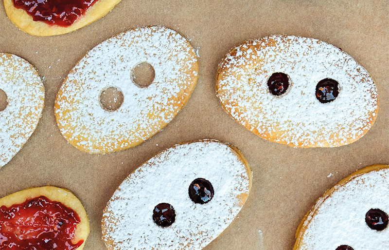Oval shaped biscuits called lunettes with jam filling and cut out holes