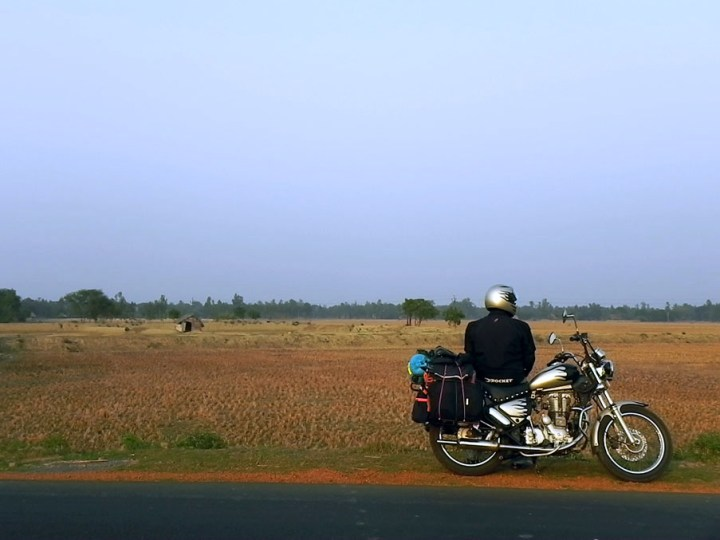 Bike rider with luggage on highway during 2000 kilometer road trip along India's east coast
