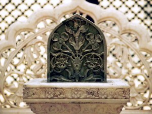 Capstone of a grave at the Paigah tombs of Hyderabad, India against a carved marble lattice