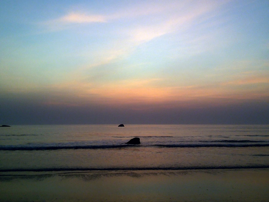 Solitary rocks at sunset on Agonda beach, Goa, India