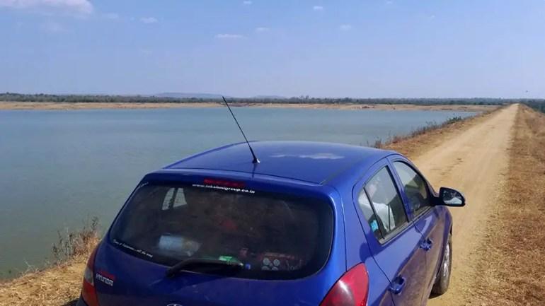 Driving over the dam at the Sarpanpally lake, Ananthagiri Hills, Vikarabad, India