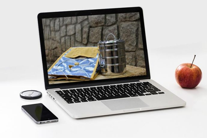 Stainless steel tiffin with blue ikat jute bag against a stone wall