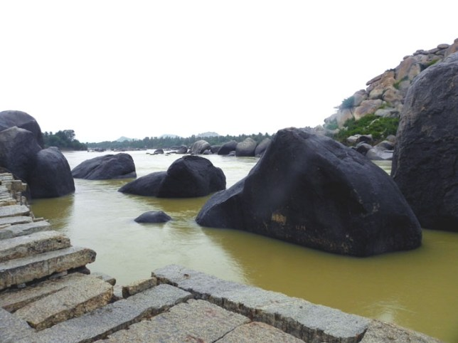 The stone walkway along the swollen river