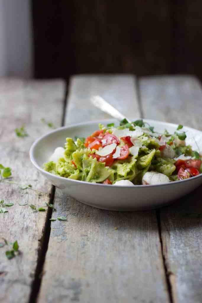 Caprese pasta salad with asparagus pesto in a white bowl