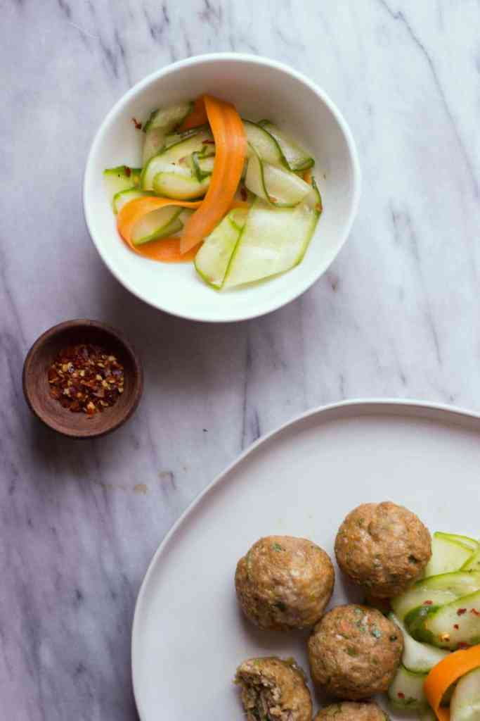 Overhead shot of Asian-Style Pork Meatballs with Sesame Cucumber Salad and a small wooden bowl with red pepper flakes.