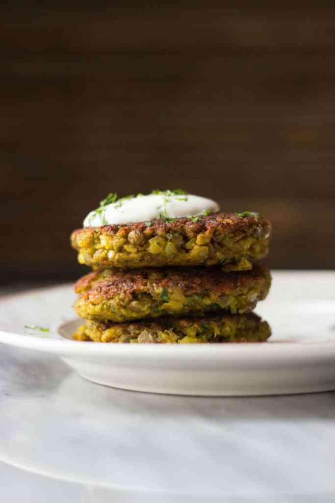 Side view of cooked lentil cakes with Greek yogurt and fresh herbs on top.