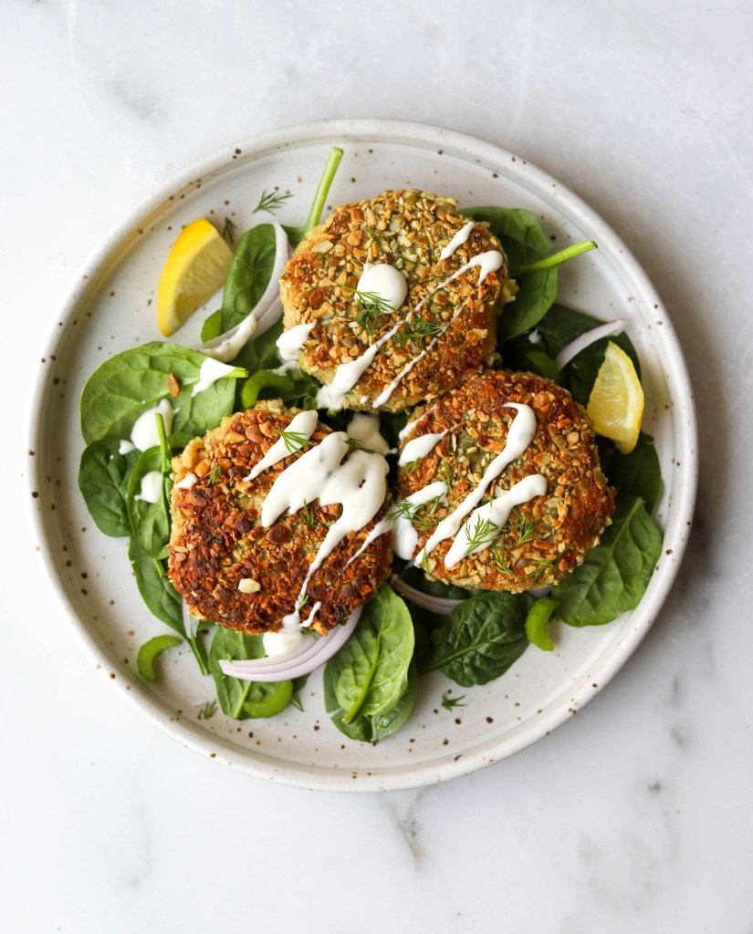 Overhead shot of pepita-crusted tuna cakes on a bed of spinach in a white plate.