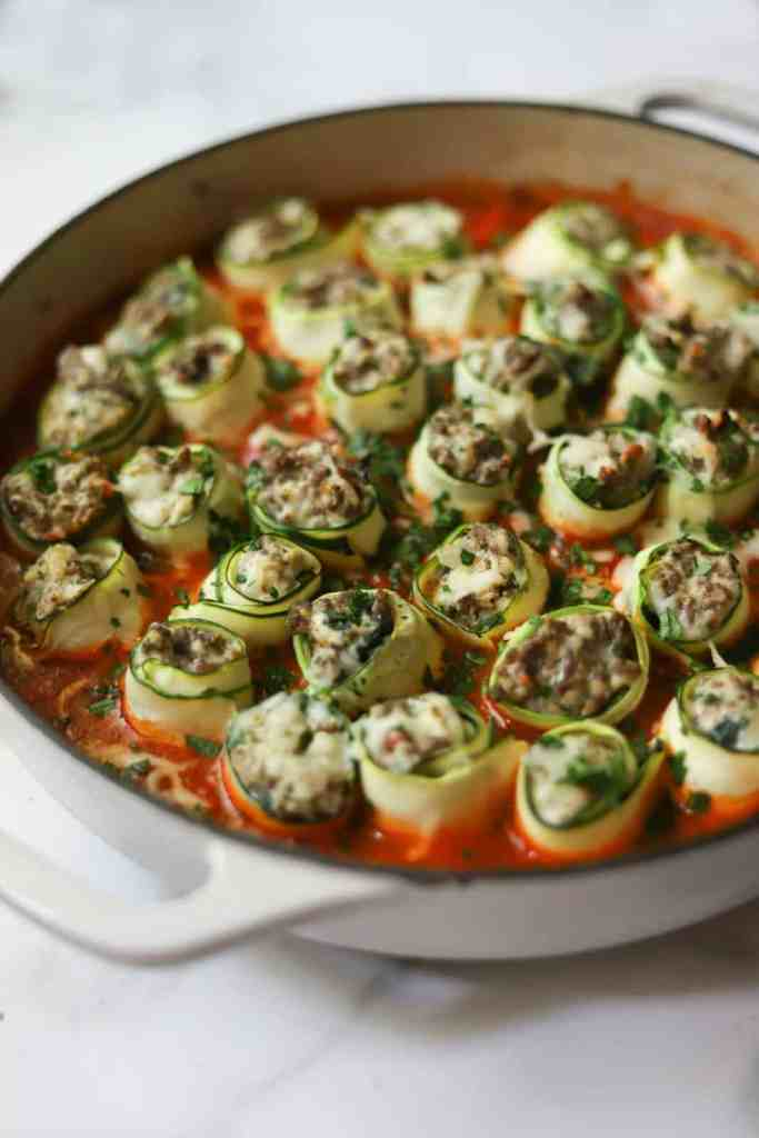 Ricotta & Beef Zucchini Roll-Ups in a white pan that's healthy and made in one pot.
