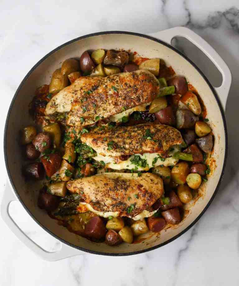 Asparagus stuffed chicken and potatoes in a white dish