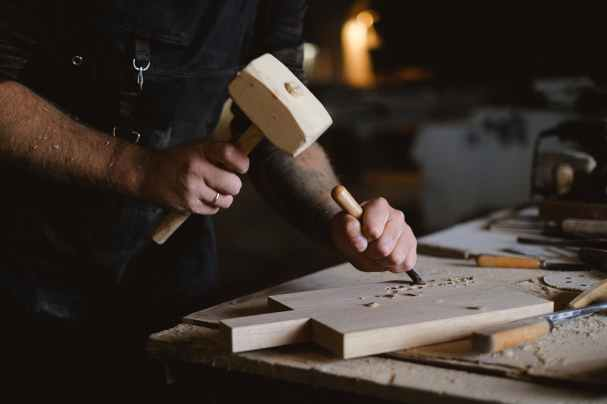 crop woodworker making patterns on wooden board