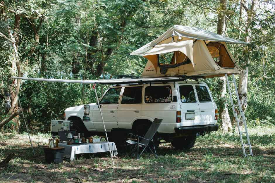 tent on roof of suv car parked in woods during camping