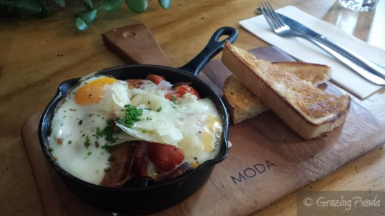 Baked Eggs with Hash Brown, Cherry Tomatoes, Olives, Spanish Onion and Basil with Toasted Pide with Chorizo