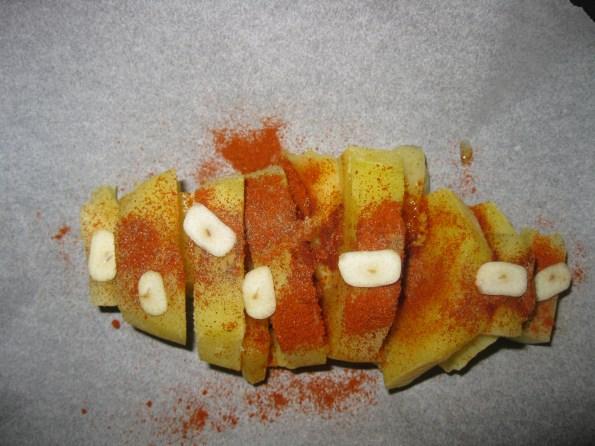 Када Вам се скува кромпир, добро га оцедите и исеците на 5 делова али не скроз до краја. Узмите неки качкаваљ који се топи па га исецкајте на коцке. Ставите између сваког парчета кромпира. Није битно ако вам се одвоји неко парче кромпира. Одозго посолите пола кашичице млевене зачинске паприке, мало бибера и ставите један чен белог лука исецкан.