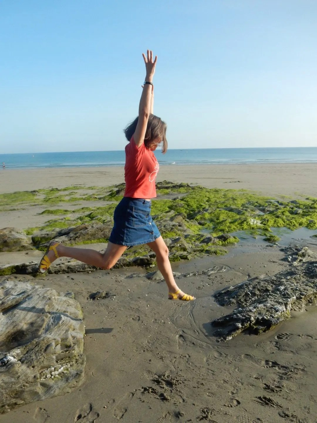 Woman leaping off a rock on the beach.