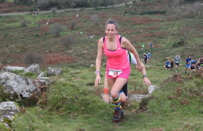 Female running reaches the top of a hill