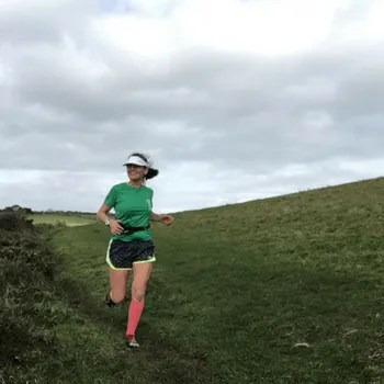 woman running along the south west coastpath