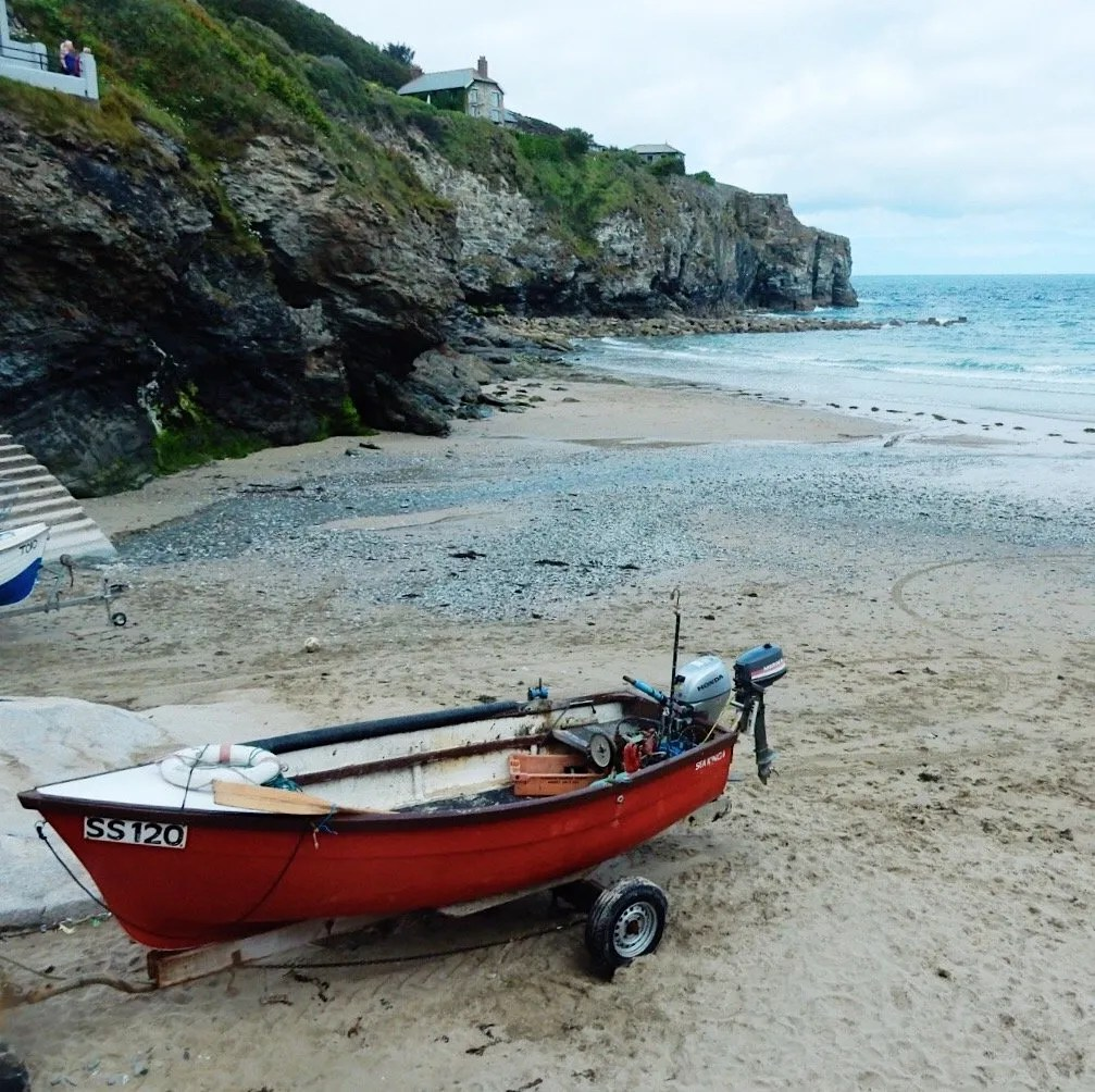 Trevaumance Cove Beach red boat and cliffs