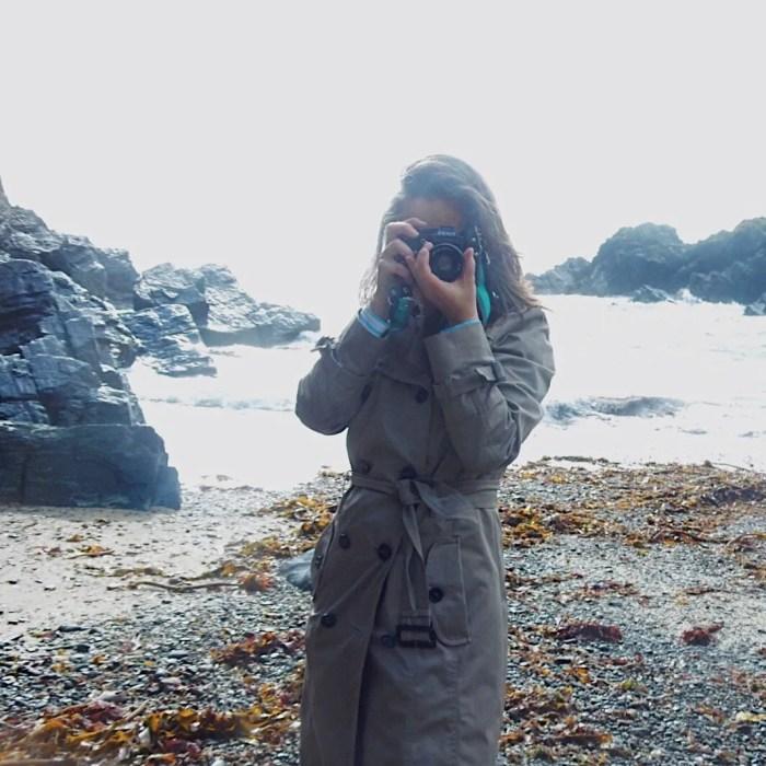 Woman holding Camera on a beach