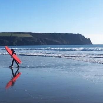 surfer walking across beach
