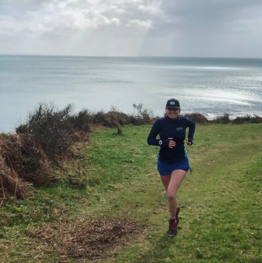 Woman running coastpath sea trail