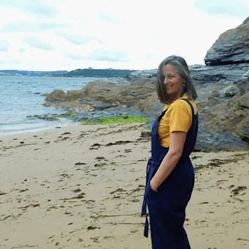 Woman standing on the beach in dungarees.