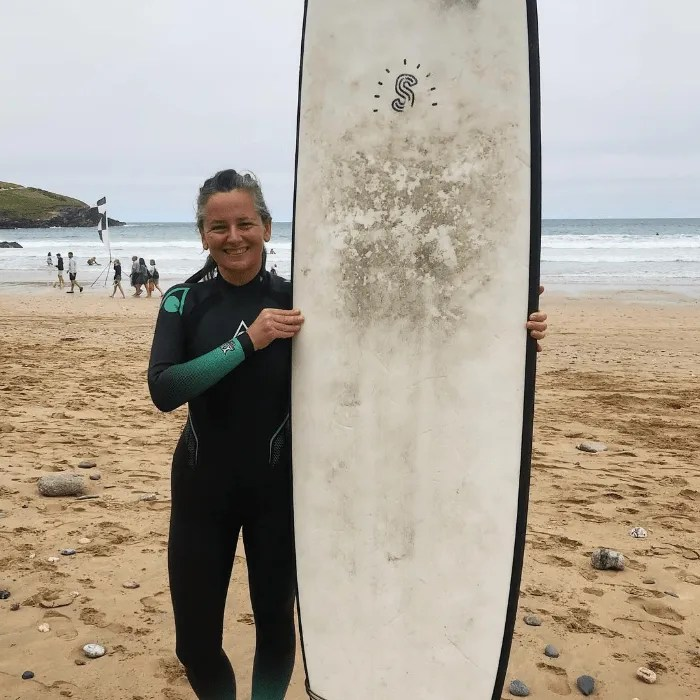 Penny Bedford from The Great Cornish Outdoors holding a surfboard