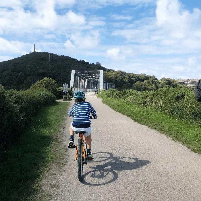 A boy cycling towards Pooley Bridge on the Camel Trail