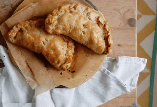 Two Cornish Pasties on a chopping board