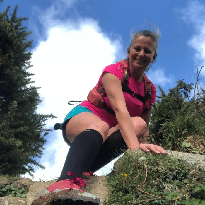 Penny Bedford climbing over a stile