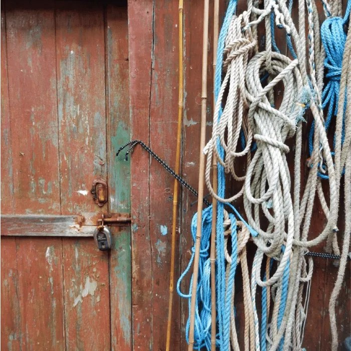 An old brown shed door with padlock with blue and white hanging rope