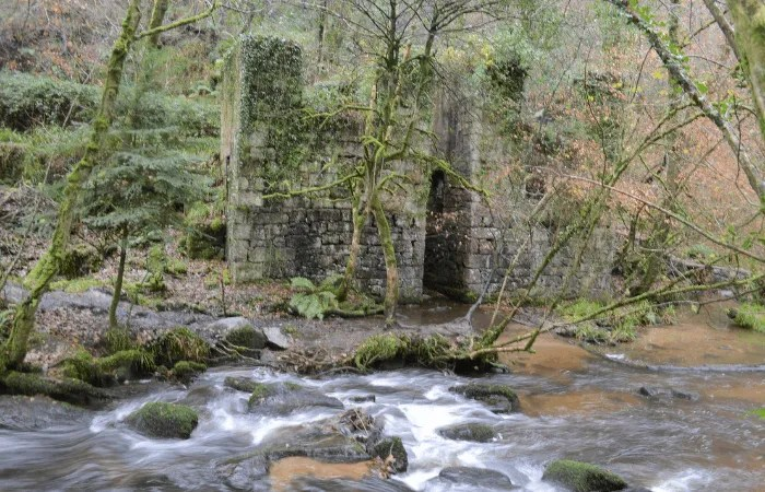 A pair of buildings in ruin next to a river