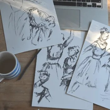 several charcoal sketches of ballerinas on a table with a cup of coffee