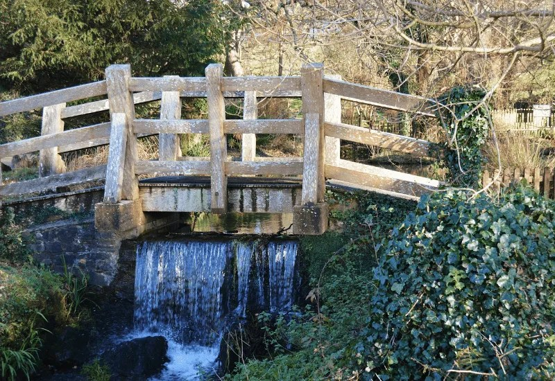 A small wooden bridge over a pond and flowing water