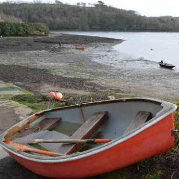 a red rowing boat on the shore at Percuil
