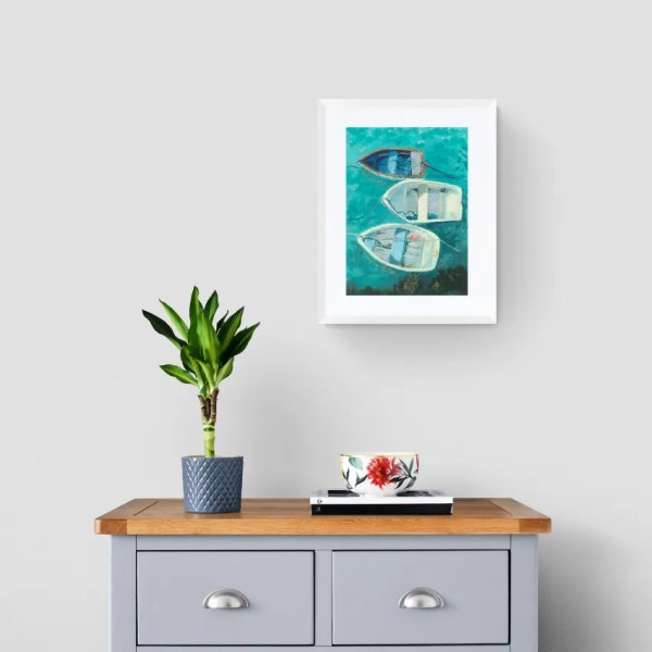 A framed print of Tri Hok on a wall above a chest of drawers and plant