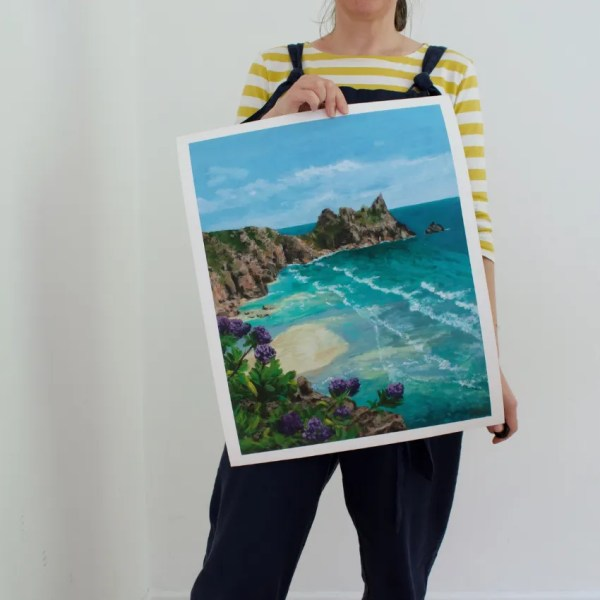 Penny sherwood standing upholding a large print of Pedn Paradise