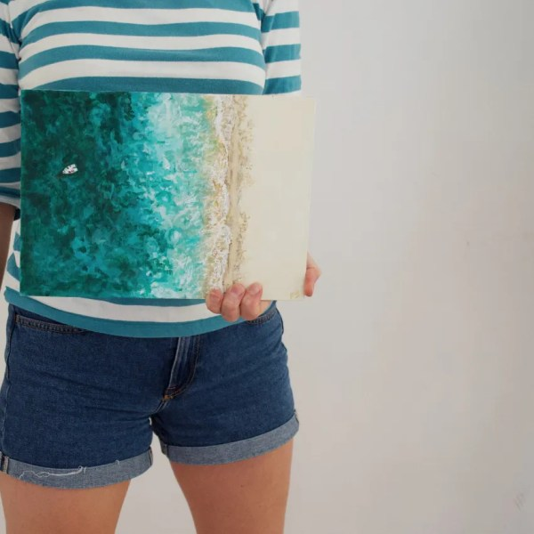 the torso of a woman in denim shorts and stripy top holding a painiting
