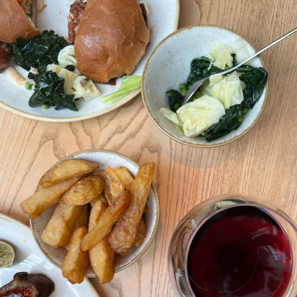 a bowl of chip, a bowl of greens and a sliced jackfruit burger on a white plate