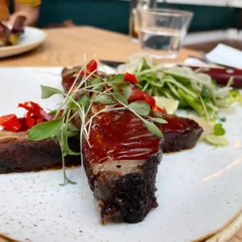 two slices of pork belly rib with sauce on a white plate at The Longstore Truro