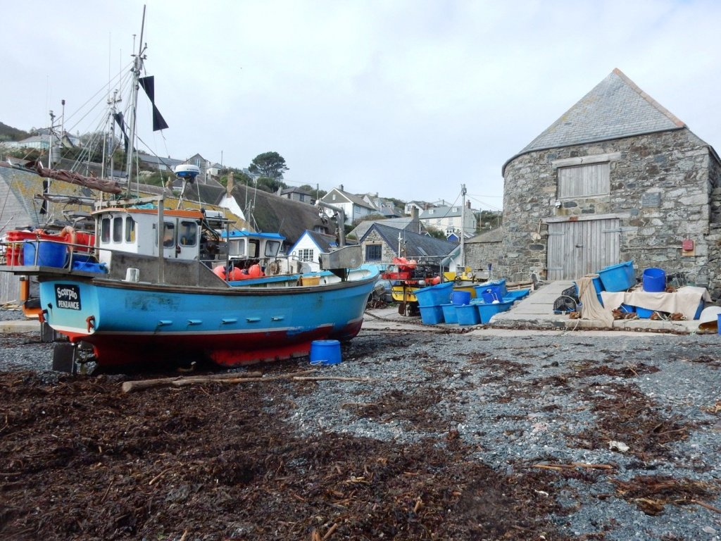 a blue fishing boat at low tide at Coverack