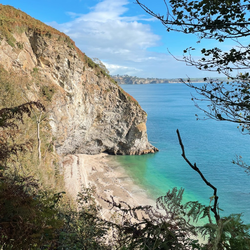 Microadventures in Cornwall finding a secluded beach like this one a small sandy cove with high yellow cliffs and turquoise sea