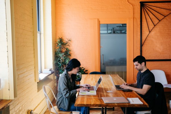 Photograph of two people in a co-working space