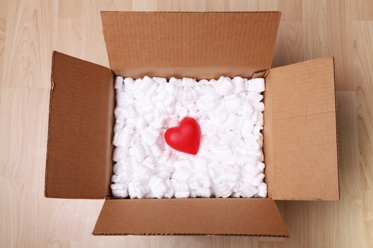 A red heart in acardboard box full of packing peanuts