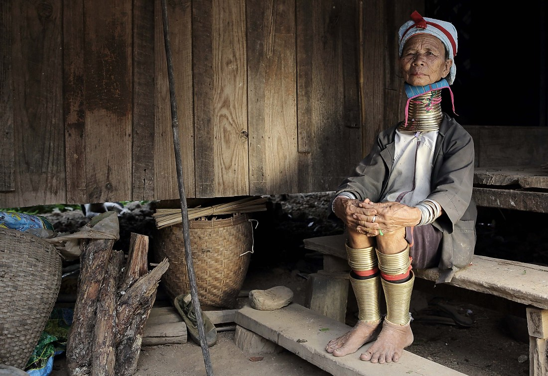 An elderly lady sits on wooden stairs covered in dust. The house appears old and without modern amenities. The lady has been worn by time, but still carry outs the tradition of neck elongation, sporting around 15 brass rings around her neck
